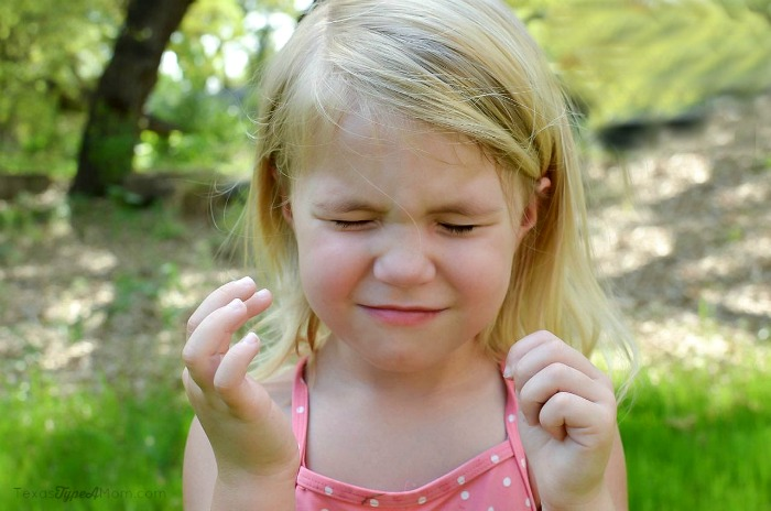 Child closing her eyes for sunscreen application
