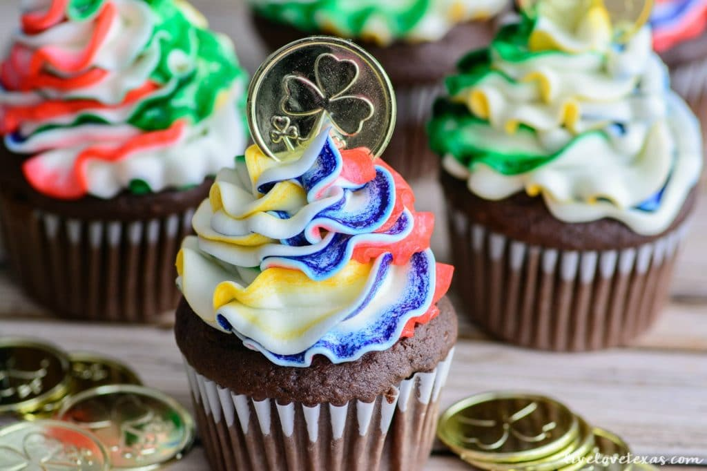Chocolate cupcakes with rainbow frosting topped with a toy gold coin.