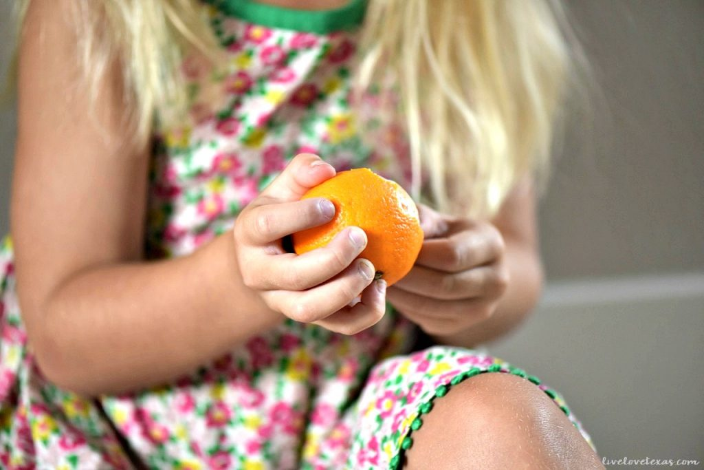 Preschooler peeling clementine