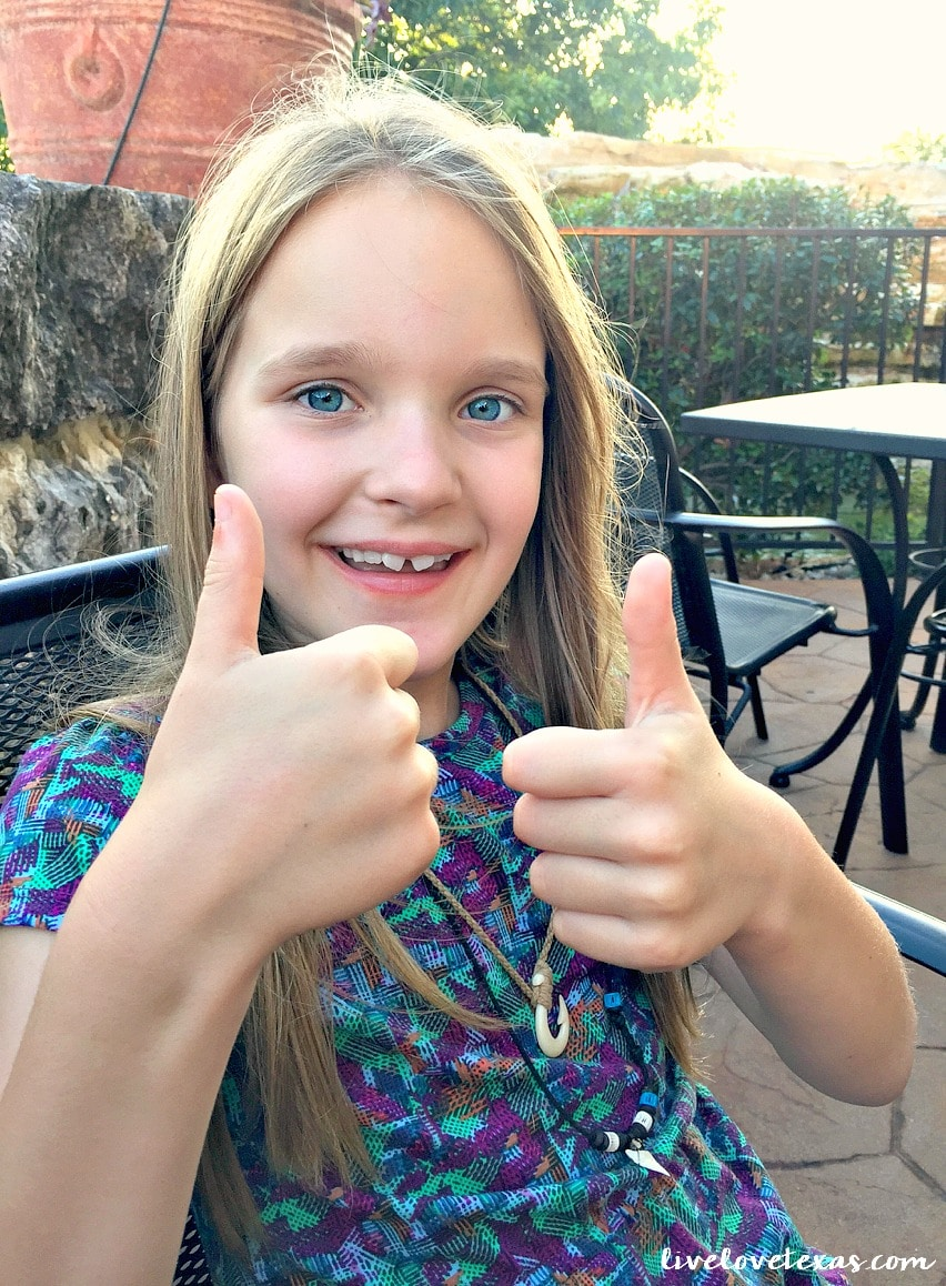 Girl giving two thumbs up to Cheddar's Scratch Kitchen review.