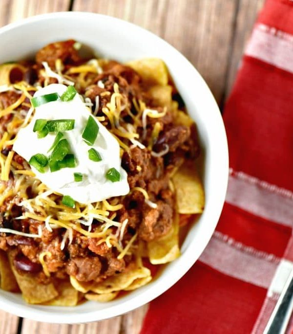 This easy crockpot chili recipe is the perfect midweek dinner or perfect for tailgating. Plus, learn how to turn your leftovers into Frito Pie on day two!