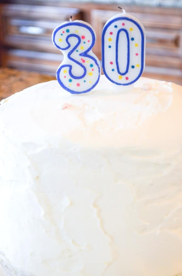 White buttercream frosted rainbow layer cake for 30th birthday party with candles.