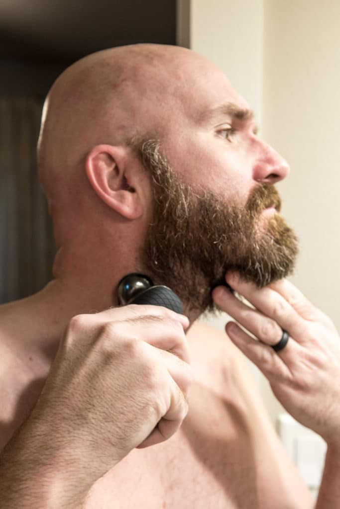 Bald man fading beard with Philips Norelco S9000 electric shaver.