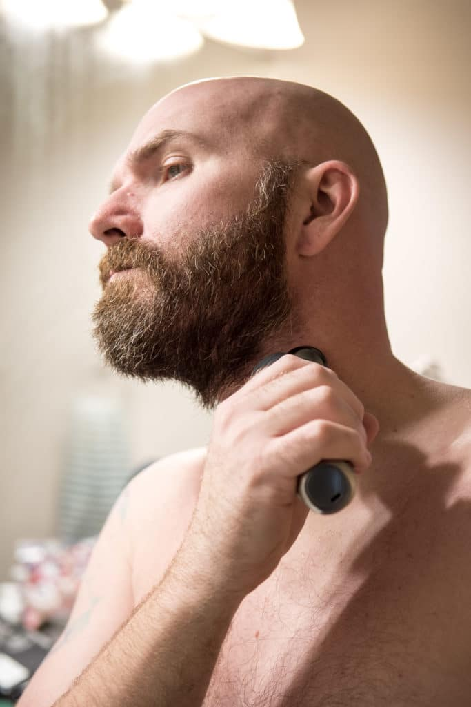 Bald man shaving beard with Norelco beard trimmer.