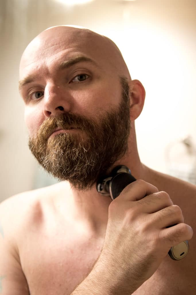 Bald man shaving beard with Philips Norelco beard trimmer.