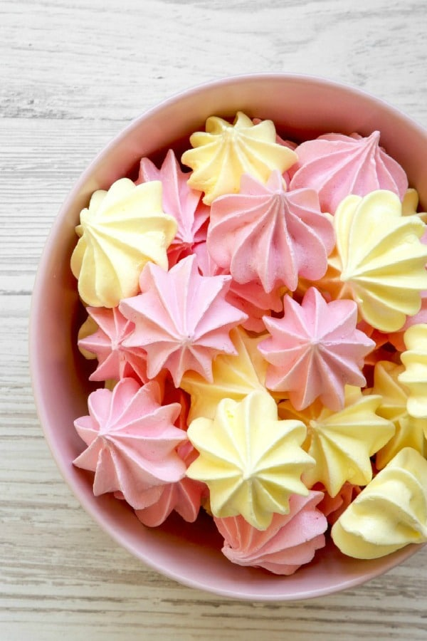 Meringue drops on wood background and in pink bowl.