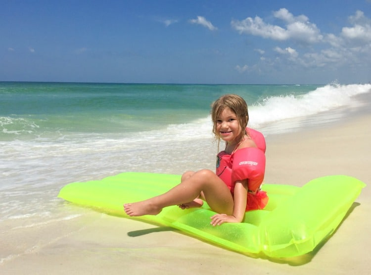 Preschool girl wearing life vest on beach