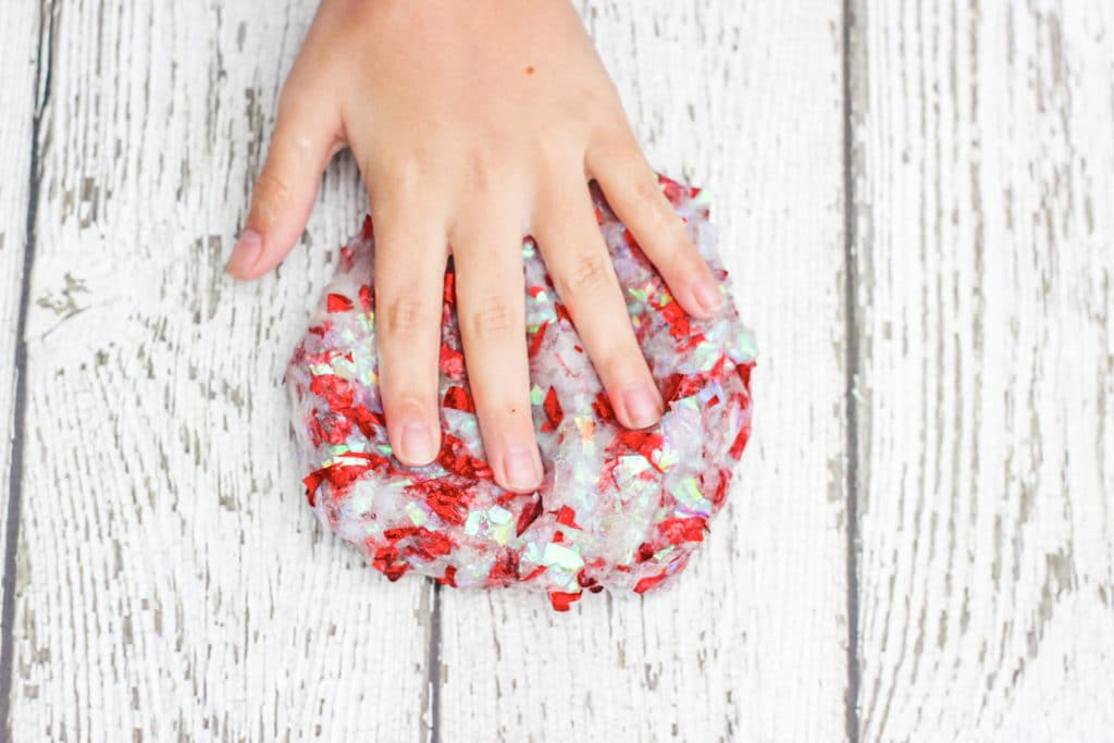 Girls hand on top of homemade slime with confetti