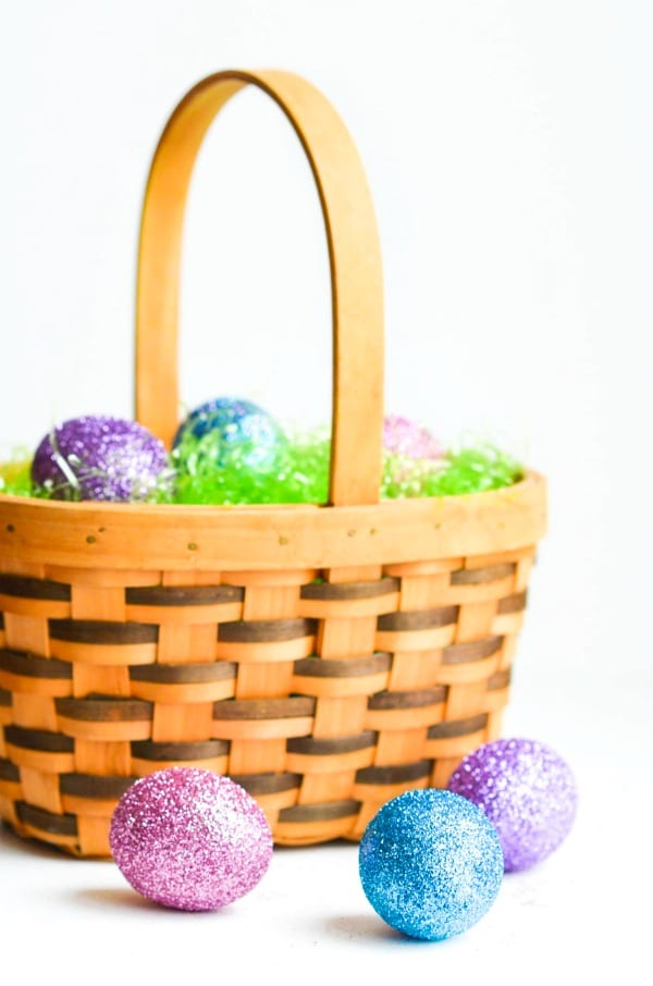 Basket of grass with glitter Easter eggs.