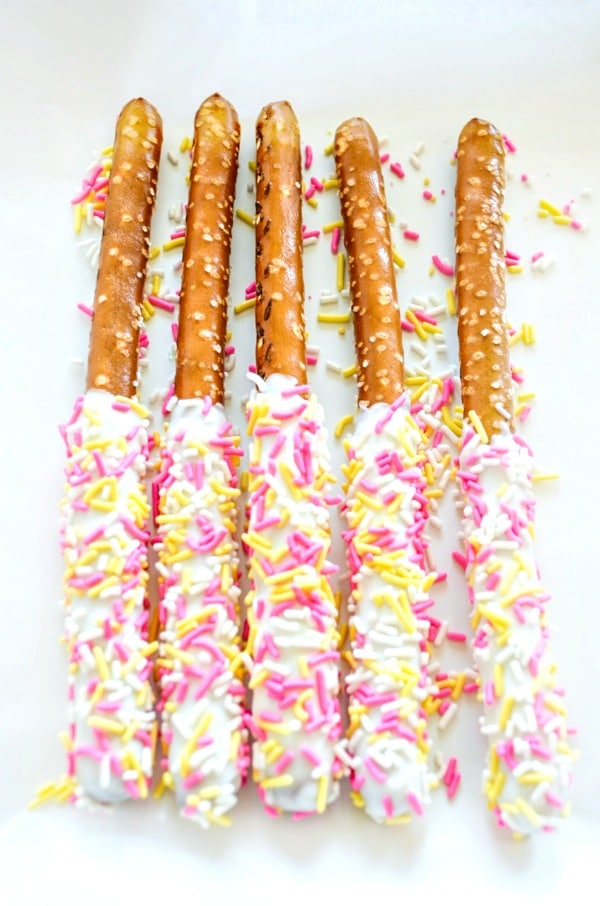 White chocolate coated pretzels with sprinkles on plate.