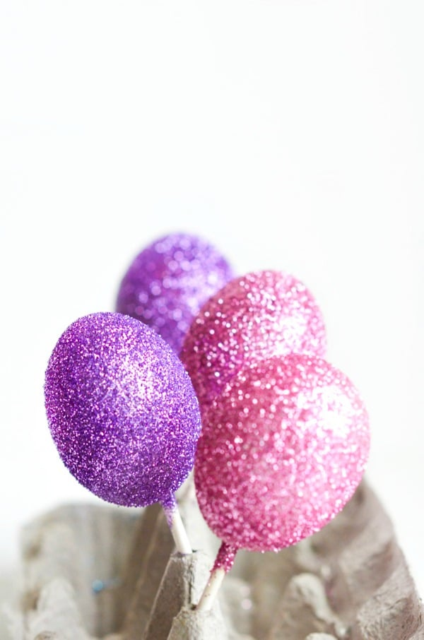 decorated glitter eggs drying on sticks in egg carton