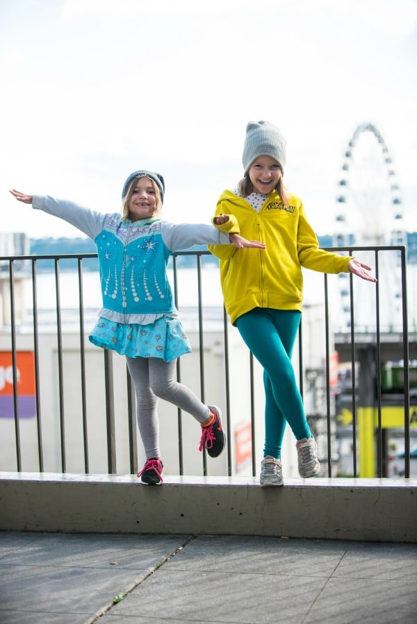 Two girls having fun in front of the Great Wheel in Seattle, Washington.
