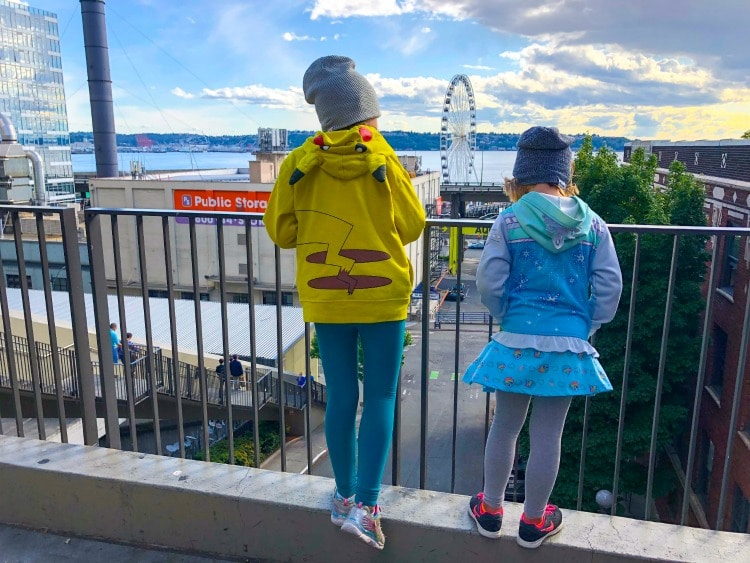 Young girls looking at water in Seattle, Washington with Great Wheel in background.