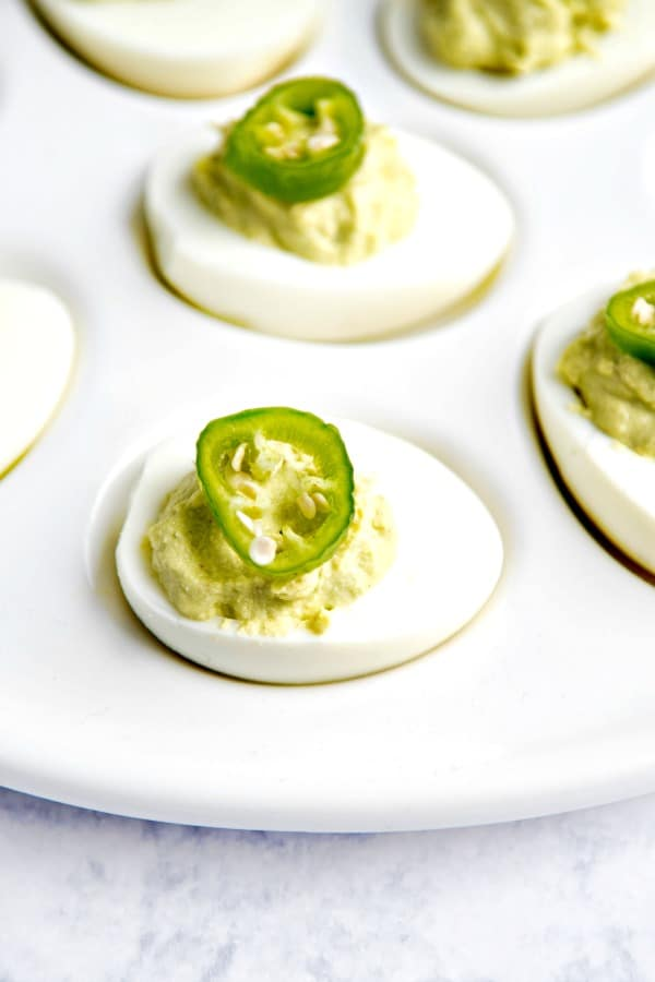 Guacamole deviled eggs on white platter.