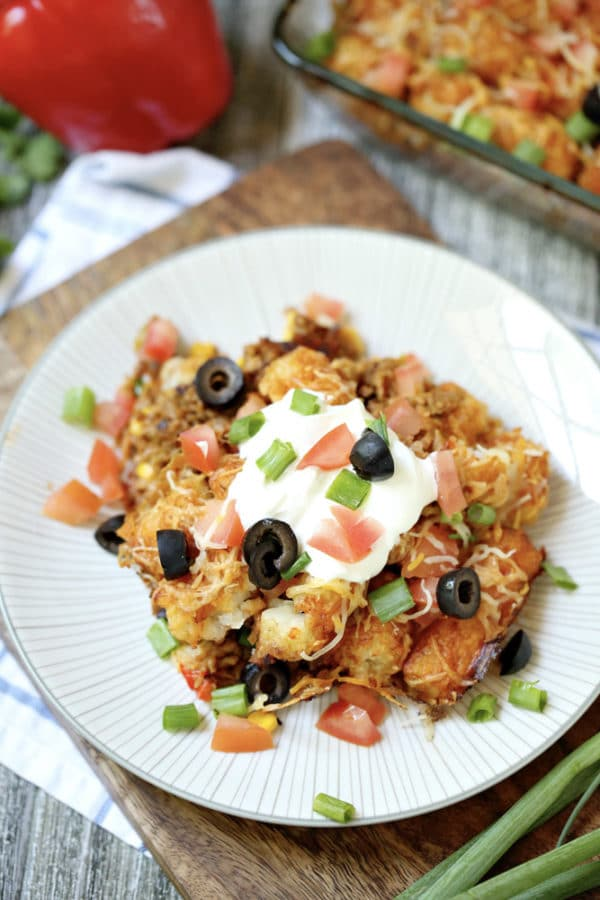 Plate of baked cheesy taco tater tot casserole with ground beef