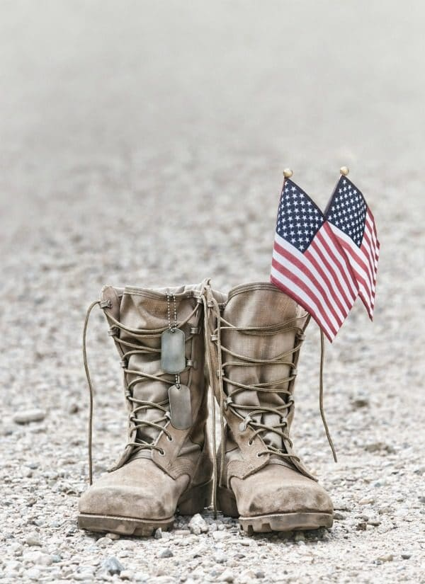 Military boots with American flags and dog tags on ground for Memorial Day