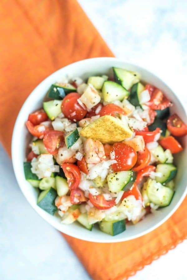 Avocado shrimp cucumber and tomato salad in bowl.
