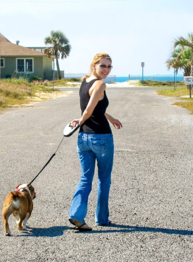 Woman walking an English Bulldog near the beach.