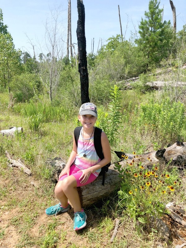 Girl sitting on burned pine log in Bastrop State Park