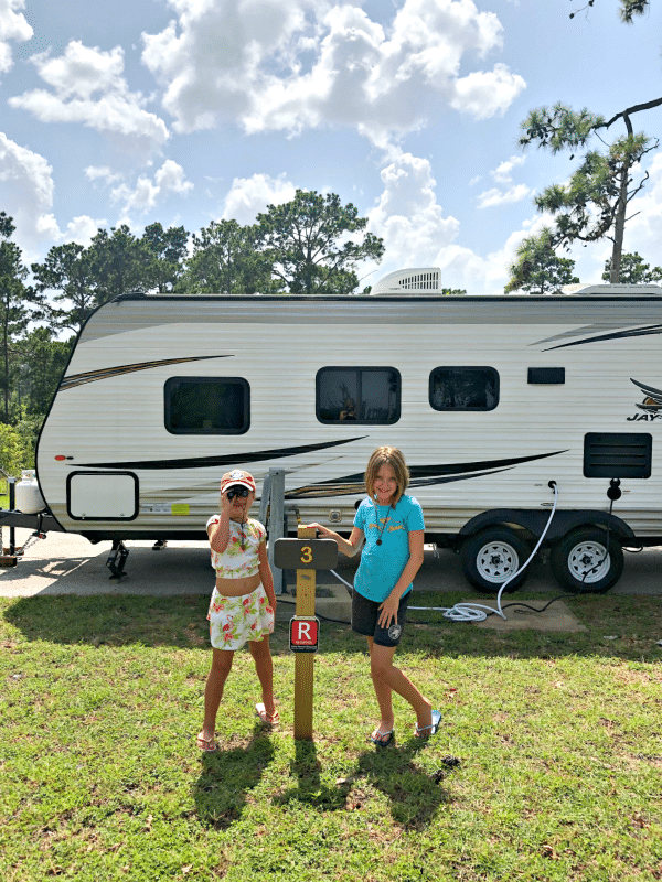 Travel trailer with girls posing in front of it at Bastrop State Park