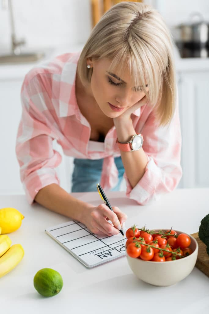 Woman meal planning with grocery list in kitchen