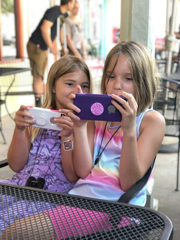 Girls sitting together playing educational apps on cell phones.
