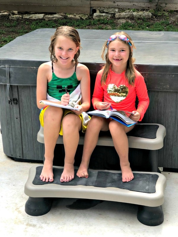 Girls reading and writing outside during summer in swimsuits to avoid summer slide.