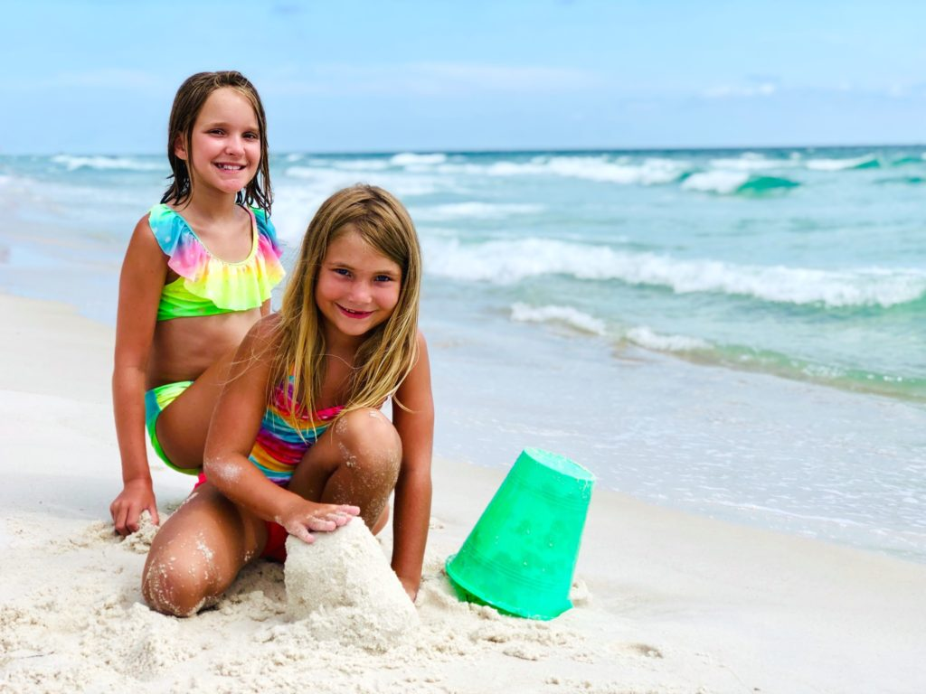 Two sisters playing in the sand on the beach.