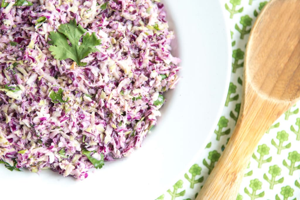 Low Carb Coleslaw in bowl with wooden serving spoon