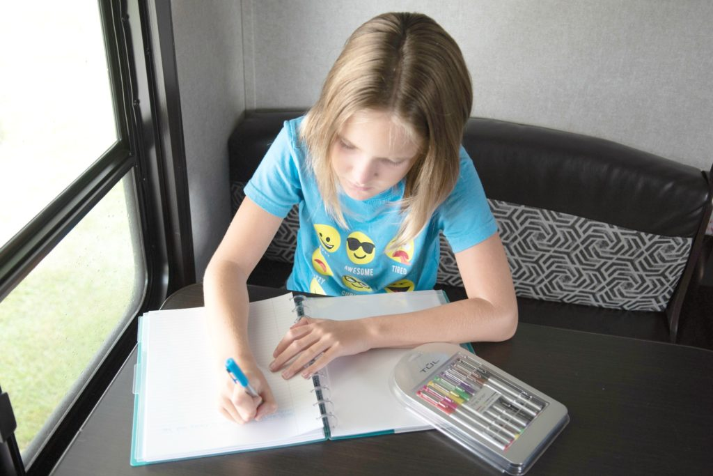 Young girl with ADHD taking notes to brain dump and color coding.