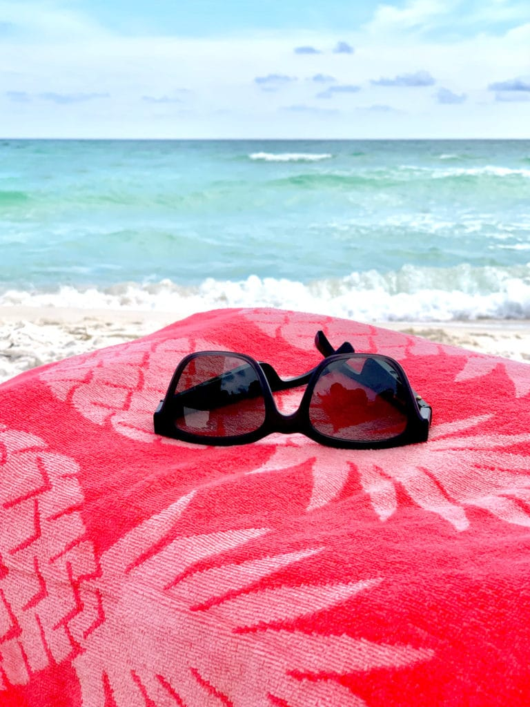 Bose bluetooth sunglasses Wayfarer style on towel at the beach.