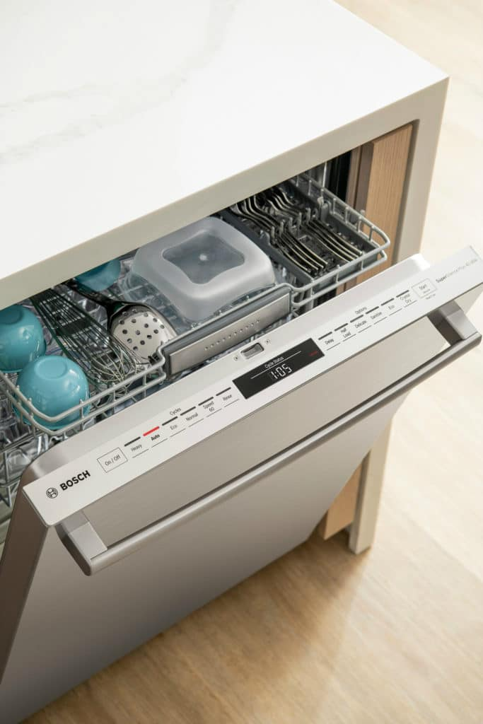 How to load a dishwasher: dishwasher open with organized top drawer.