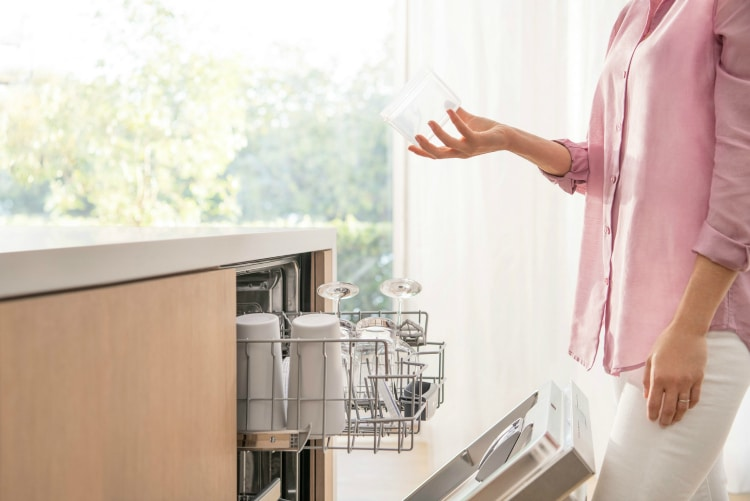 Woman unloading dishes from Bosch 500 Dishwasher.