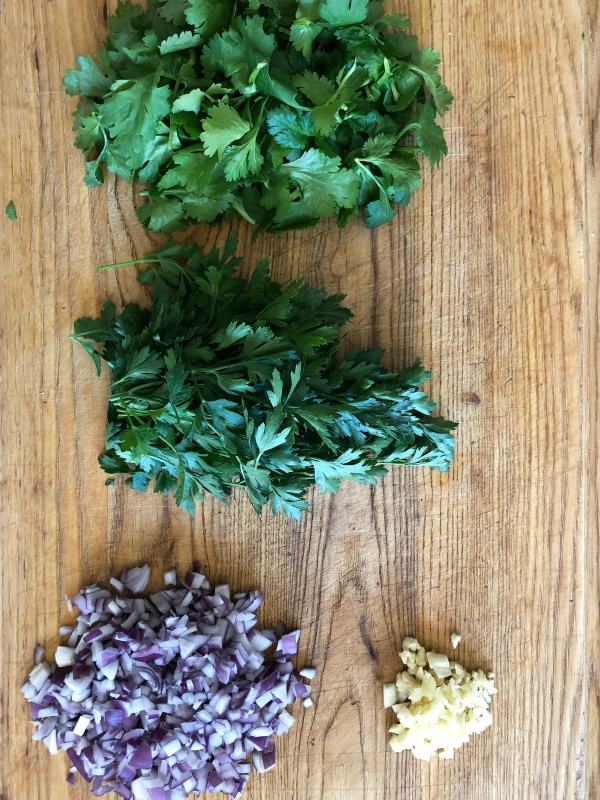 cilantro parsley onion garlic on cutting board for chimichurri sauce