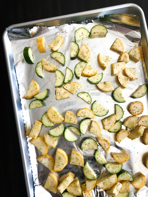 Chopped squash and zucchini on sheet pan for roasting