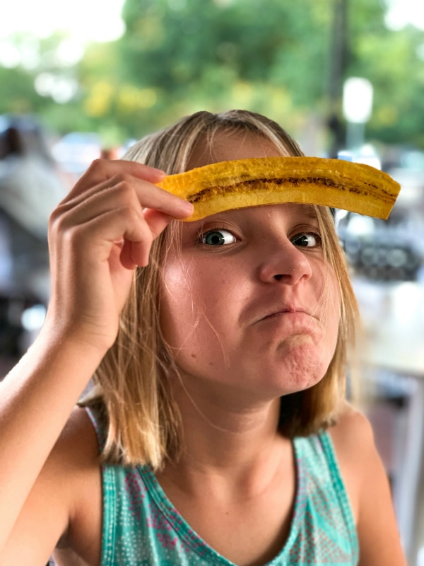 girl posing with plantain eyebrows at restaurant