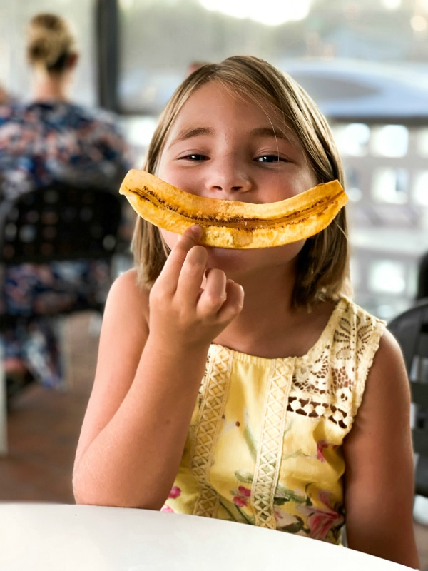 girl posing with plantain smile at restaurant
