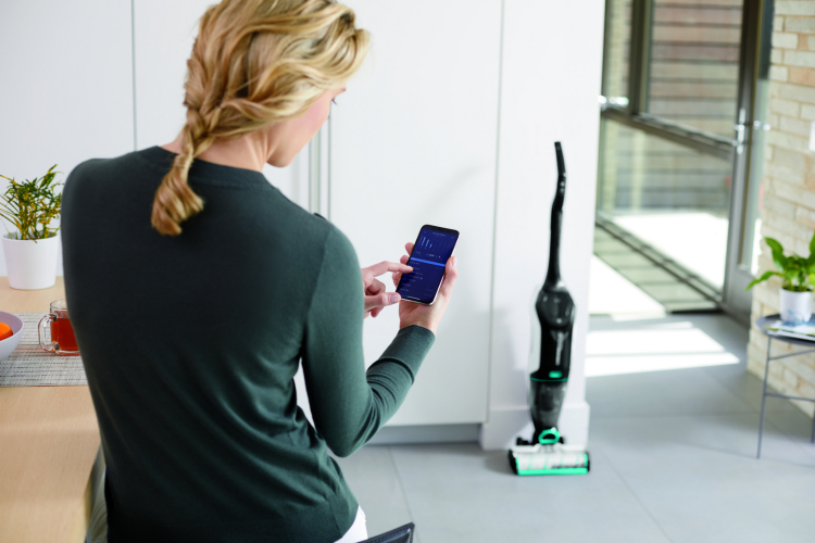 Lazy girl using her app to track her cleaning habits on the Bissell Crosswave for floors.