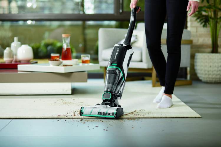 Woman vacuuming and moppinga the same time on multiple surfaces with the Bissell Crosswave Max Cordless Vacuum.