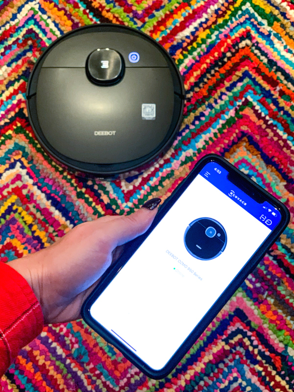 Woman's hand holding phone with robotic vacuum app in front of colorful rug with robotic vacuum.