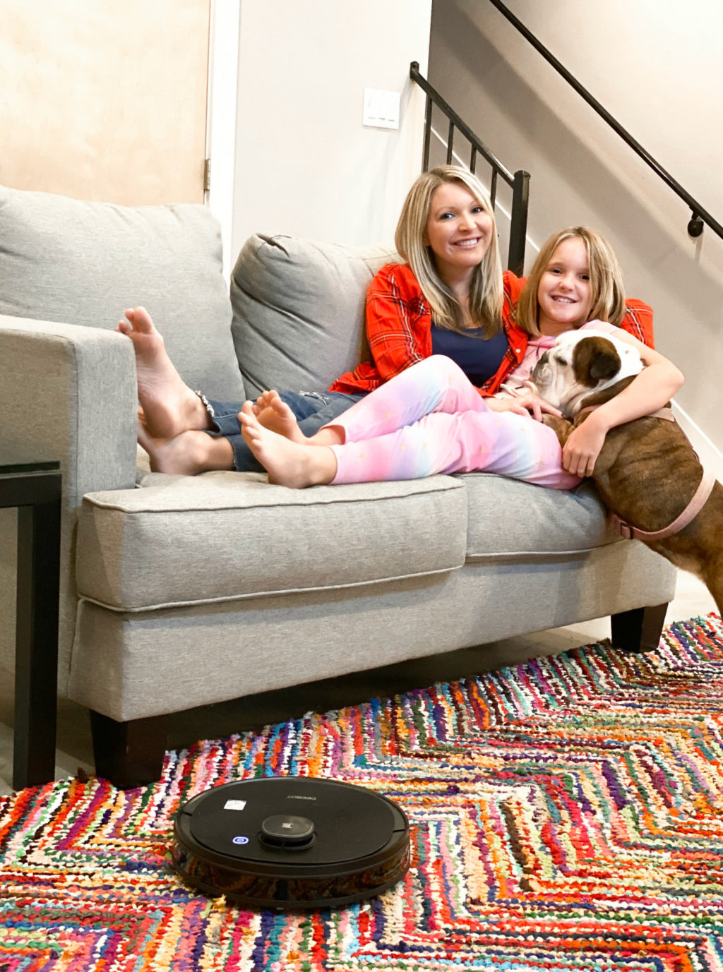 Mom and daughter on couch with dog on colorful rug and robotic vacuum.