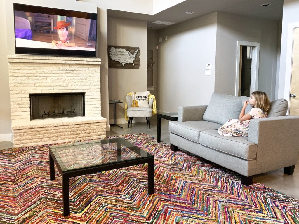 Young girl watching Toy Story 4 on TV with colorful rug