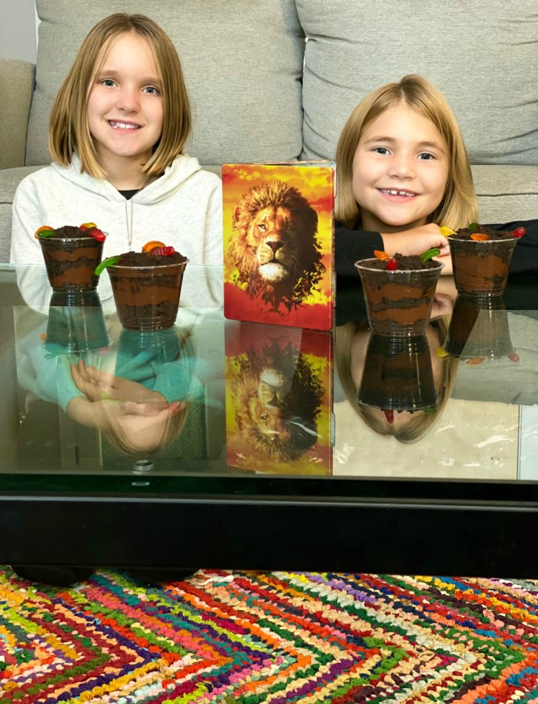 Sisters sitting on colorful rug with Lion King movie and inspired dirt cup dessert recipe.