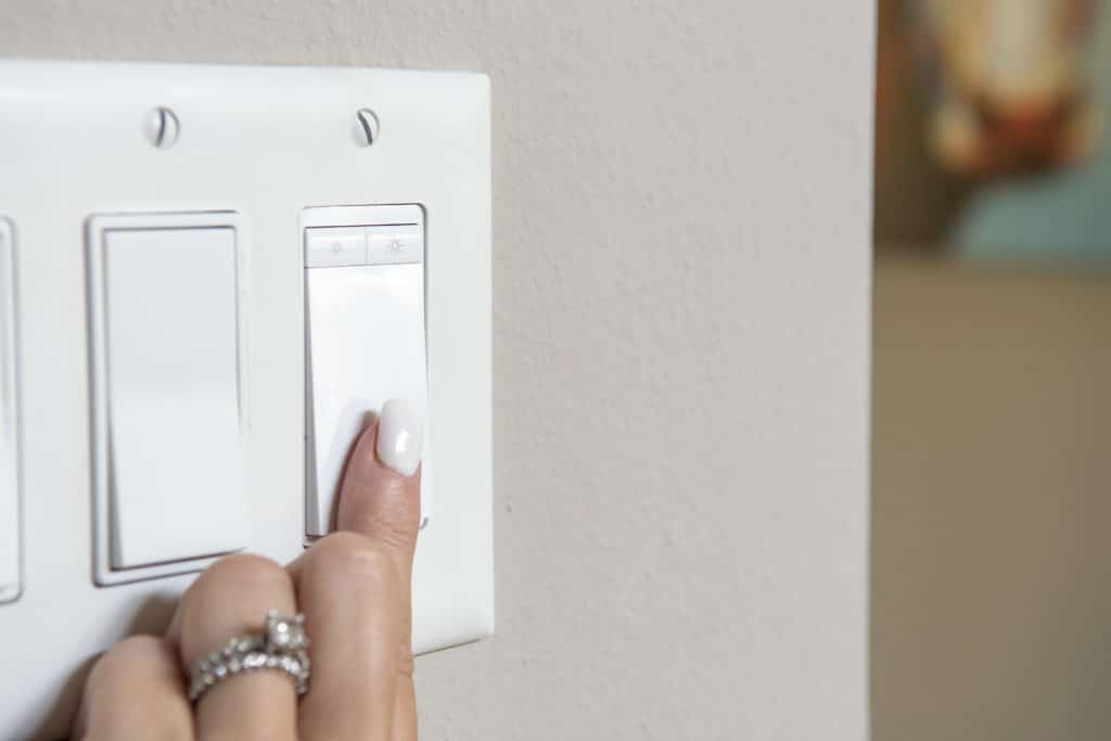 Manicured finger turning on Kasa Light Switch Wifi Dimmer