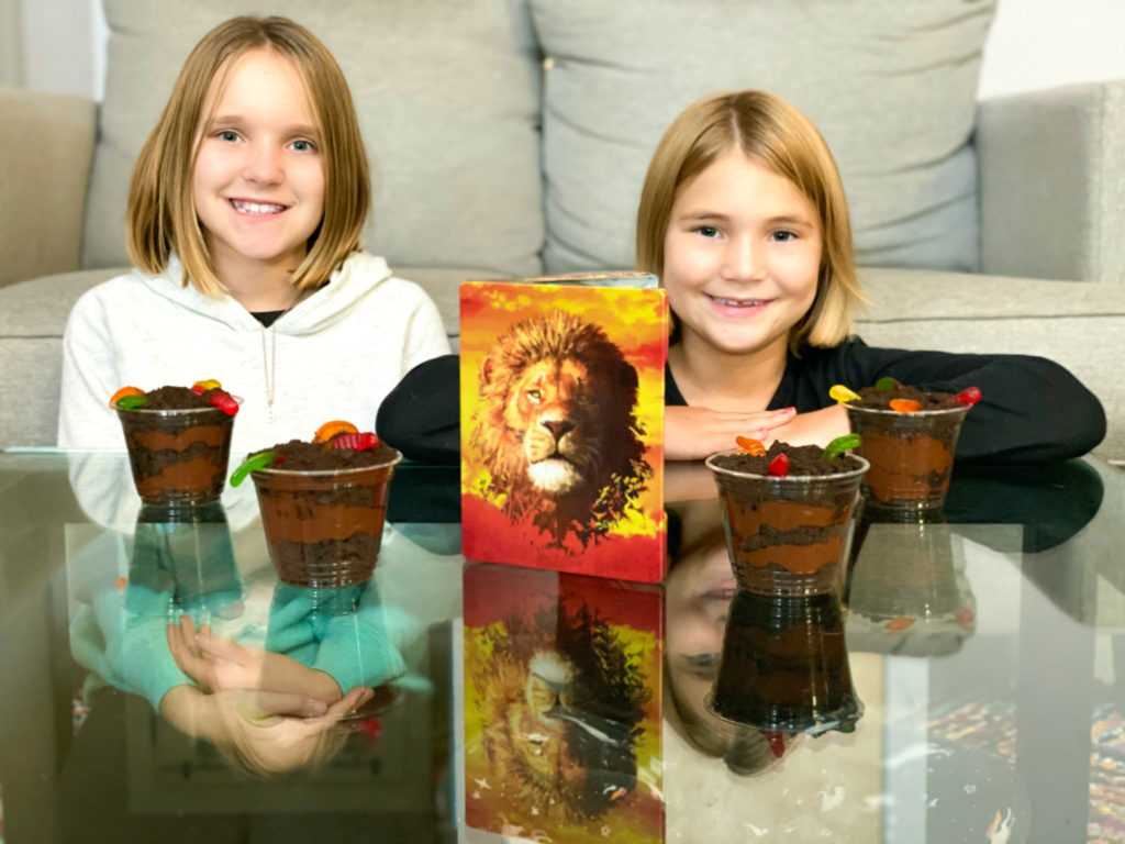 Girls watching The Lion King with dirt cup pudding on table in front of them.