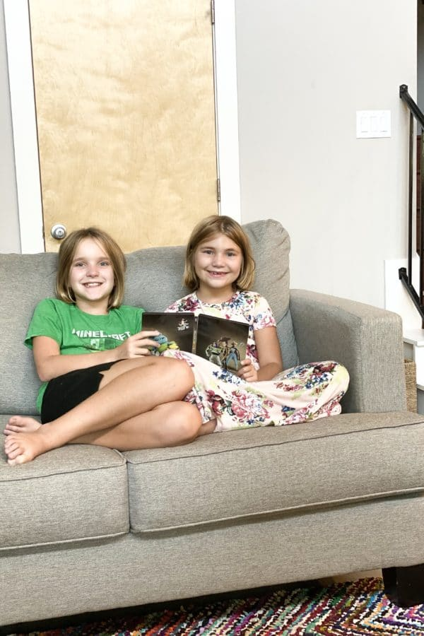 Sisters sitting on loveseat together holding Toy Story 4 DVD