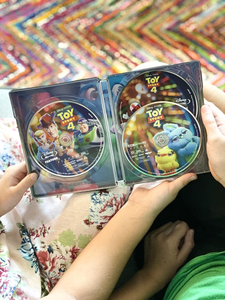 Girls holding Toy Story 4 Steelbook DVD on couch