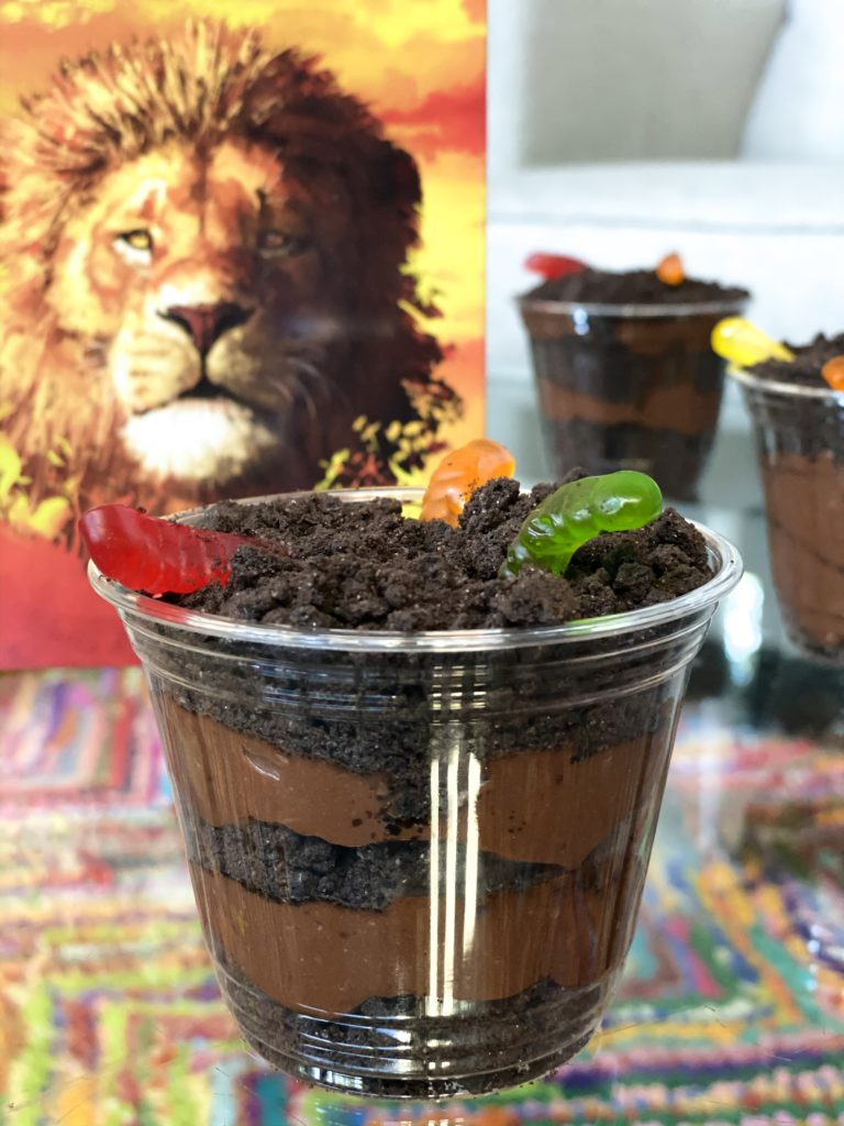 Lion King recipe of Dirt Cups with Gummy Worms on table closeup.