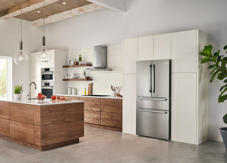 Modern kitchen with natural cabinets, white counters, and counter depth stainless steel fridge.