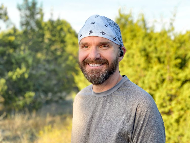 Man smiling before running in front of trees with wireless earbuds in his ears.
